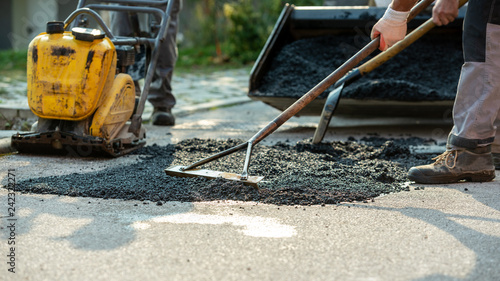 Fotografia  Low angle view of two workers arranging fresh asphalt mix with rakes and shovel