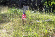 American Military Solider Grave. American Flag On A Tombstone In An Overgrown Cemetery.
