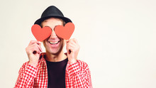 Man In Love. Happy Man Covered His Eyes By Red Hearts, Isolated On White. Copy Space. Happy Valentine Day. Funny Man In Black Hat With Valentine Cards. Love Is Blind. Dreamy Man With Paper Hearts.