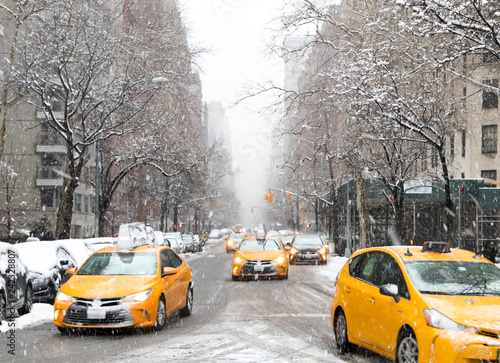New York City taxis drive down Fifth Avenue through the snow during a winter bli Wallpaper Mural