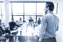 Business Man Making A Presentation At Office. Business Executive Delivering A Presentation To His Colleagues During Meeting Or In-house Business Training. Rear View. Blue Toned.