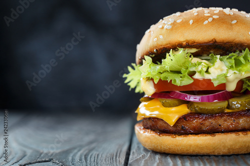 Fotografia Close-up of delicious fresh home made burger with lettuce, cheese, onion and tom