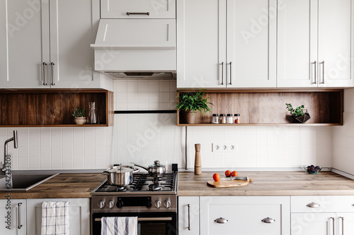 Photo Cooking food on modern kitchen with furniture in grey color and wooden tabletop
