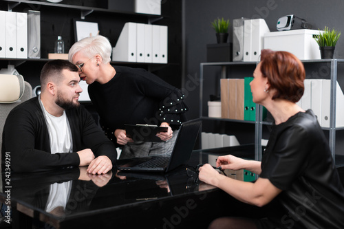 Business woman whispers something to man in ear with another young girl