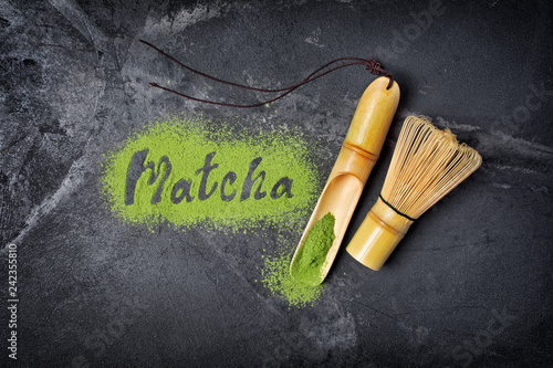 Lettering from green matcha tea with bamboo scoop and whisk on black background