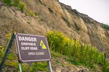 """Danger, Unstable Cliff Edge"" Sign On The Pacific Ocean Coastline, California"