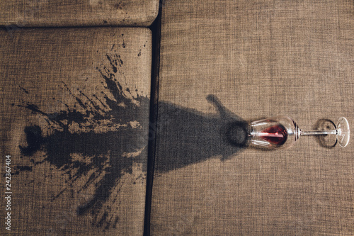 Red wine spilled on a grey couch sofa. Wallpaper Mural