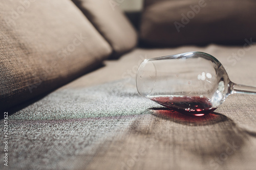 Fotografering  Red wine spilled on a grey couch sofa.