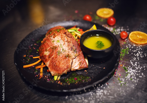 Close up of delicious tuna steak on crunchy vegetables. On plate little bowl of soup, too.