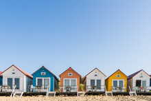 Multi Colored  Beach Houses In A Row Under A Blue Sky On A Sunny Day