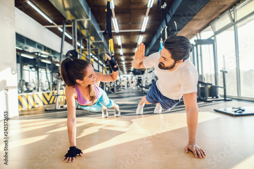 Poster Fitness Sporty couple doing push-ups and giving high five. Gym interior.