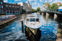 View On The Bridge Through The River Channel With Boat In Front, Typical Picture Of Canals In Amsterdam