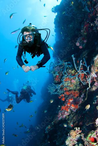 Scuba Diver explores coral reef.