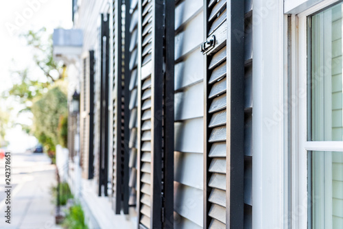 Fotografie, Obraz  Black decorative row of window shutters closeup architecture open exterior of ho