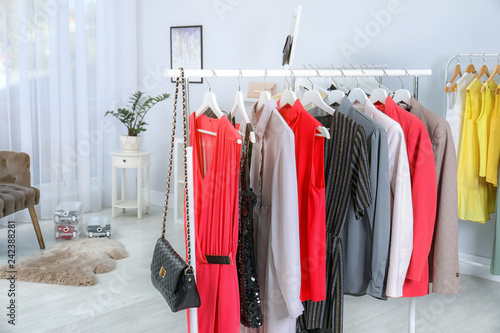 Fotografía  Wardrobe racks with different stylish clothes in light room