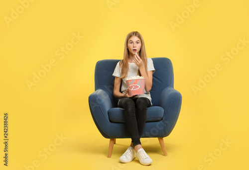 Emotional teenage girl with popcorn sitting in armchair during cinema show on color background