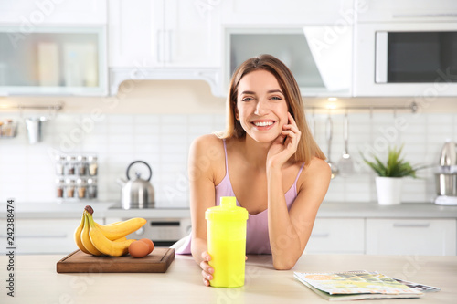 Stampa su Tela Young woman holding bottle of protein shake at table with ingredients in kitchen