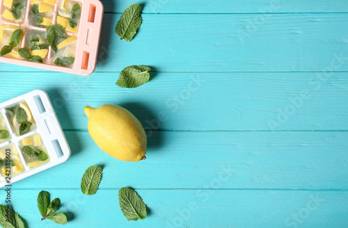 Flat lay composition with ice cube tray, mint and lemon on wooden background. Space for text