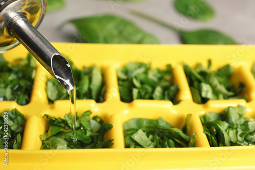 Pouring oil into ice cube tray with spinach, closeup