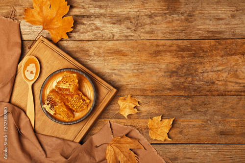 fototapeta na drzwi i meble Flat lay composition with spoon of honey and combs on wooden background. Space for text