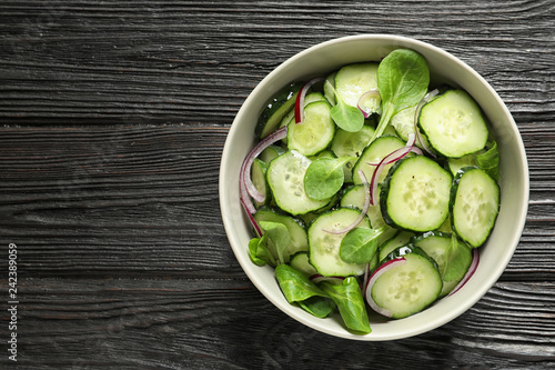 Delicious cucumber salad with onion and spinach in bowl on wooden background, top view. Space for text