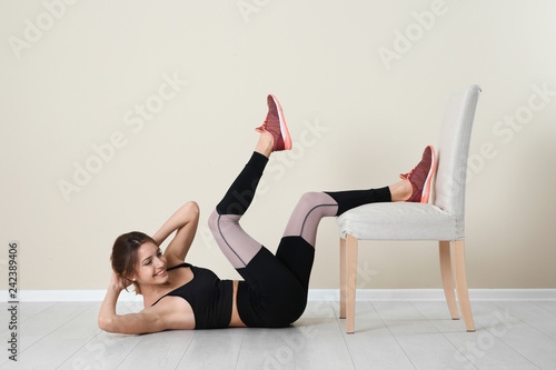 Foto auf AluDibond Gymnastik Young woman exercising with chair near color wall. Home fitness