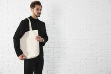 Young Man Holding Textile Bag Against Brick Wall.  Mockup For Design