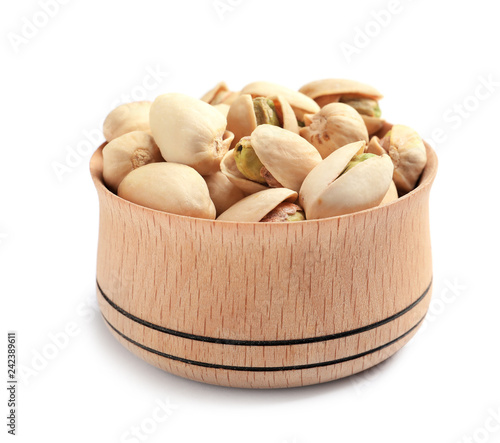 Organic pistachio nuts in wooden bowl isolated on white, closeup