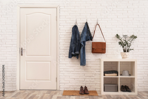 Stylish hallway interior with door, comfortable furniture and clothes on brick wall