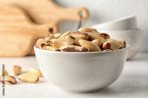 Bowl with tasty Brazil nuts on white table