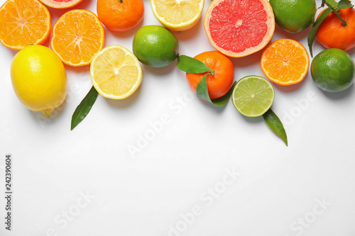 Different citrus fruits on white background, top view. Space for text