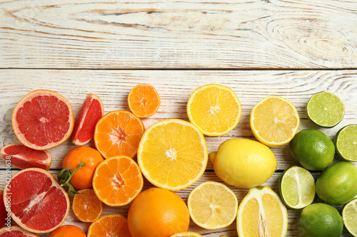 Different citrus fruits on wooden background, top view. Space for text