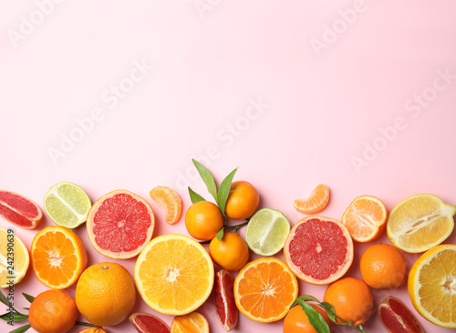 Tuinposter Vruchten Different citrus fruits on color background, top view. Space for text