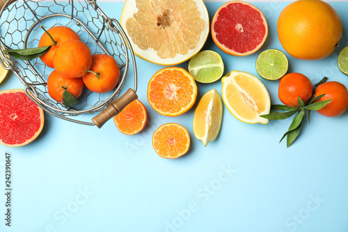 Different citrus fruits on color background, top view. Space for text
