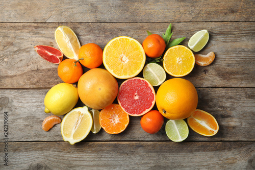 Different citrus fruits on wooden background, top view