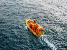 Industrial Yellow Boat With Group Of Unrecognizable Workers In Orange Uniform Coveralls In Ocean Water, Aerial View