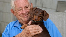 Happy, Smiling Senior Man Holding His Dog