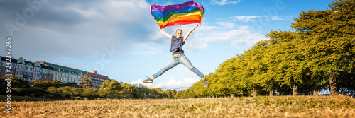 Fotomural A young happy woman jumps in a summer park with a rainbow flag in her hands, a symbol of LGBT, equal rights and freedoms for people with homosexual orientation