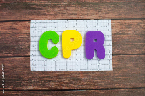 Fotografía  Color alphabet in word CPR abbreviation of Cardiopulmonary resuscitation lies on a printed cardiogram of the heart on wood background