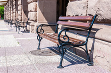 Outdoor Street Benches Made Of Curved Forged Metal And Wood Standing In A Row Near Facades