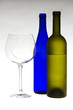 Glass of wine and bottles on light gray