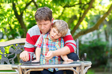 Little Kid Boy And His Young Father Playing Together Checkers Game. Child And Man Spending Leisure Together. Family Having Fun In Summer Garden Outside