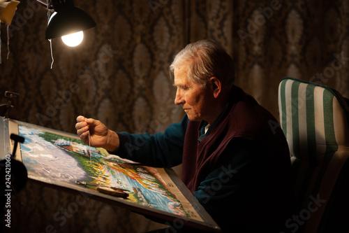 Fotografering Elderly man woving a tapestry under bright light in living room on winter evenin