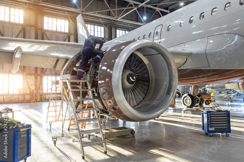 Poster Avion à Moteur Mechanic specialist repairs the maintenance of engine of a passenger aircraft in a hangar