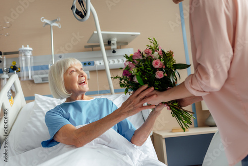 Photo daughter presenting flowers to smiling senior woman lying in bed in hospital