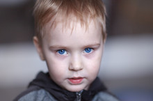 Close Up Portrait Of Cute Caucasian Baby Boy With Very Serious Face Expression. Bright Blue Eyes, Fair Hair. Strong Emotions. Indoors, Copy Space.
