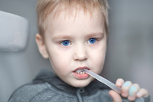 Close Up Portrait Of Cute Caucasian Baby Boy With Very Serious Face Expression Cleaning The Teeth With Teeth Brush, By Himself. Bright Blue Eyes, Fair Hair. Indoors, Copy Space.