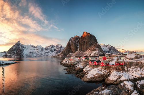 Red house fishing village with snow mountain at sunset