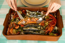 Crop Hands Taking Seafood Dish From Pan