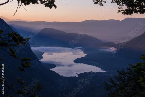 Fotobehang Volle maan Lake Bohinj in morning mist from Komna